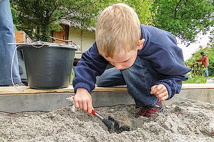 Junge beim archäologischen Graben mit Pinsel im Sand